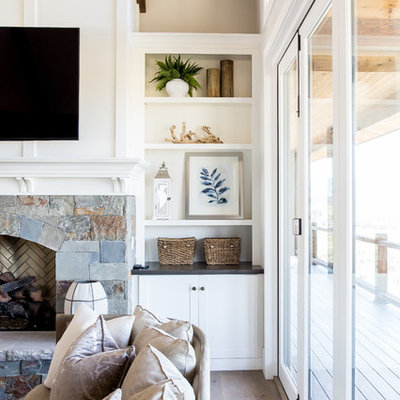 Inspiration for a large country open concept medium tone wood floor living room remodel in Salt Lake City with white walls, a standard fireplace, a stone fireplace and a wall-mounted tv