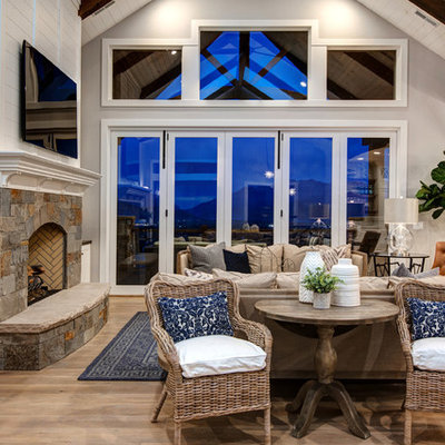 Example of a large farmhouse open concept medium tone wood floor living room design in Salt Lake City with white walls, a standard fireplace, a stone fireplace and a wall-mounted tv