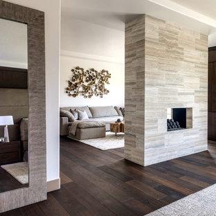 Foto di un ampio soggiorno moderno chiuso con pareti bianche, pavimento in gres porcellanato, camino bifacciale, cornice del camino piastrellata e TV a parete