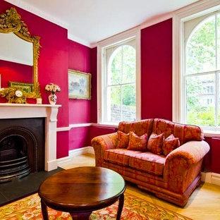 サンフランシスコの中サイズのコンテンポラリースタイルのおしゃれなリビング (ライブラリー、赤い壁、淡色無垢フローリング、標準型暖炉、石材の暖炉まわり、テレビなし) の写真