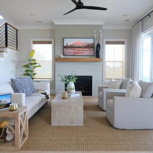 Idée de décoration pour un salon marin de taille moyenne et ouvert avec un mur gris, un sol en bois brun, une cheminée standard, un manteau de cheminée en lambris de bois et un téléviseur fixé au mur.