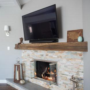ロサンゼルスの中サイズのビーチスタイルのおしゃれなLDK (グレーの壁、無垢フローリング、コーナー設置型暖炉、石材の暖炉まわり、壁掛け型テレビ) の写真