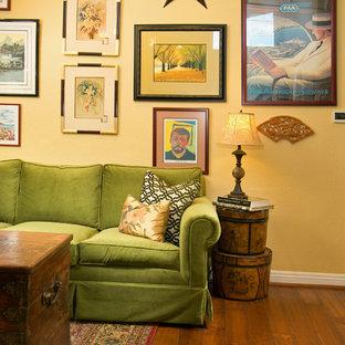 Immagine di un soggiorno boho chic di medie dimensioni e stile loft con pareti gialle, pavimento in legno massello medio, nessun camino, nessuna TV, pavimento marrone e sala formale