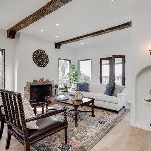 ロサンゼルスの中くらいの地中海スタイルのおしゃれなLDK (フォーマル、白い壁、淡色無垢フローリング、標準型暖炉、石材の暖炉まわり、テレビなし、茶色い床) の写真
