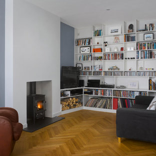 Living room - contemporary open concept medium tone wood floor living room idea in London with a wood stove, a plaster fireplace and a tv stand