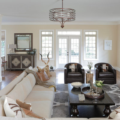 Large country open concept medium tone wood floor living room photo in Atlanta with beige walls, a wall-mounted tv, a standard fireplace and a brick fireplace