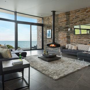 Diseño de salón abierto, contemporáneo, grande, con suelo de baldosas de porcelana, chimeneas suspendidas y suelo gris