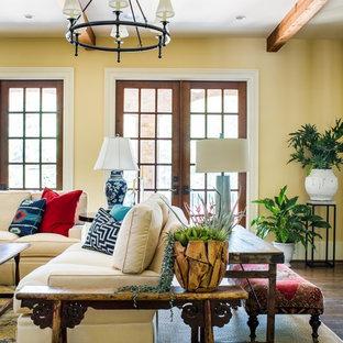 アトランタの大きいサンタフェスタイルのおしゃれなLDK (壁掛け型テレビ、黄色い壁、濃色無垢フローリング、標準型暖炉、コンクリートの暖炉まわり) の写真
