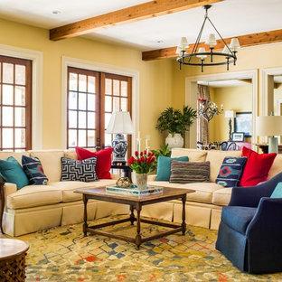 Großes, Offenes Klassisches Wohnzimmer mit gelber Wandfarbe, dunklem Holzboden, Kamin, Kaminsims aus Beton und Wand-TV in Atlanta