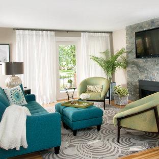 Ejemplo de salón abierto, actual, pequeño, con paredes beige, suelo de madera clara, chimenea de doble cara, marco de chimenea de piedra y televisor colgado en la pared