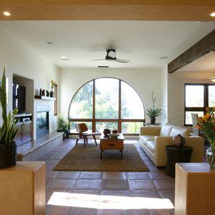 Réalisation d'un salon méditerranéen de taille moyenne et ouvert avec un mur multicolore, un sol en carreau de terre cuite, une cheminée standard, un manteau de cheminée en plâtre, un téléviseur encastré, une salle de réception et un sol rouge.