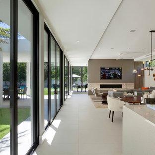 マイアミの大きいミッドセンチュリースタイルのおしゃれなLDK (グレーの壁、磁器タイルの床、横長型暖炉、壁掛け型テレビ) の写真