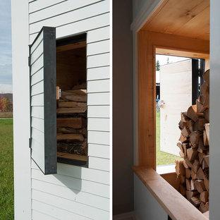 Diseño de salón abierto, de estilo de casa de campo, de tamaño medio, sin televisor, con paredes grises, suelo de madera en tonos medios, estufa de leña y marco de chimenea de piedra