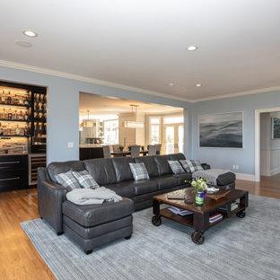 Imagen de salón con barra de bar cerrado, moderno, grande, con paredes grises, suelo de madera en tonos medios, chimenea tradicional, televisor colgado en la pared y suelo marrón
