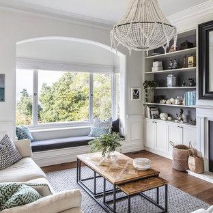 Diseño de salón abierto, clásico renovado, de tamaño medio, con paredes blancas, chimenea tradicional, suelo marrón y suelo de madera en tonos medios