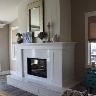 他の地域の中サイズのカントリー風おしゃれなLDK (フォーマル、標準型暖炉、グレーの壁、ラミネートの床、漆喰の暖炉まわり、テレビなし) の写真