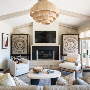 Inspiration pour un salon marin avec un mur beige, un sol en bois clair, une cheminée ribbon, un téléviseur fixé au mur et un plafond en poutres apparentes.
