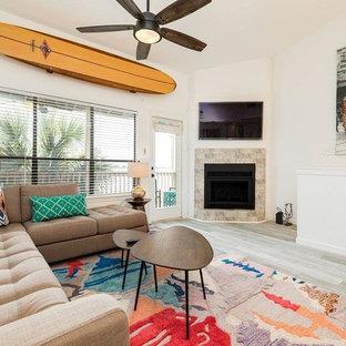 ヒューストンの中サイズのビーチスタイルのおしゃれなLDK (白い壁、磁器タイルの床、コーナー設置型暖炉、タイルの暖炉まわり、壁掛け型テレビ、ベージュの床) の写真