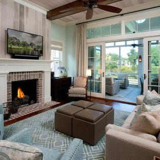 アトランタのビーチスタイルのおしゃれなリビング (青い壁、濃色無垢フローリング、標準型暖炉、レンガの暖炉まわり、壁掛け型テレビ、茶色い床) の写真