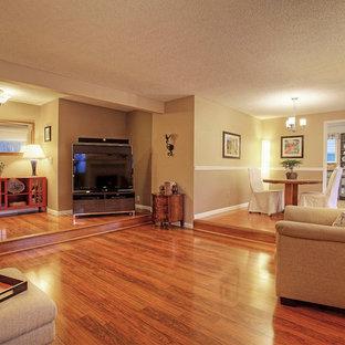 Esempio di un soggiorno tradizionale di medie dimensioni e aperto con pareti beige, pavimento in laminato, cornice del camino in legno e TV autoportante