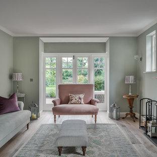 Esempio di un soggiorno tradizionale di medie dimensioni e chiuso con sala formale, pareti verdi, parquet chiaro, camino classico, cornice del camino in pietra e nessuna TV