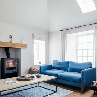 Foto de salón abierto, marinero, de tamaño medio, con paredes blancas, suelo de madera en tonos medios, estufa de leña y suelo marrón