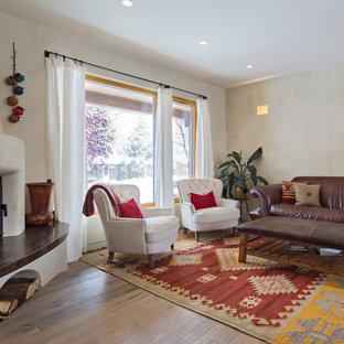 Inredning av ett medelhavsstil mellanstort separat vardagsrum, med beige väggar, mellanmörkt trägolv, en öppen hörnspis och en spiselkrans i gips