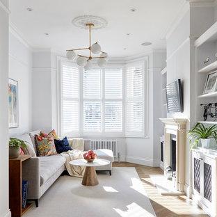 Klassisches Wohnzimmer mit weißer Wandfarbe, braunem Boden, hellem Holzboden, Kamin, Wand-TV und Kaminumrandung aus Stein in London