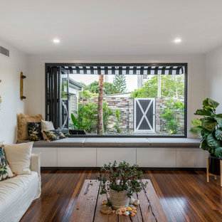 Photo of a beach style formal enclosed living room in Gold Coast - Tweed with white walls, dark hardwood floors and brown floor.