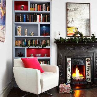 Inspiration för ett vintage vardagsrum, med ett bibliotek, vita väggar, mörkt trägolv och en standard öppen spis