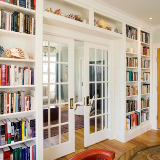 Large traditional enclosed living room in Portland Maine with a library, medium hardwood floors, a two-sided fireplace, a plaster fireplace surround and no tv.