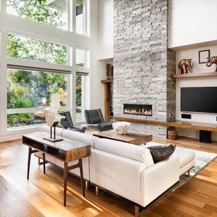 Modern inredning av ett vardagsrum, med vita väggar, mellanmörkt trägolv, en bred öppen spis, en spiselkrans i sten, en väggmonterad TV och brunt golv