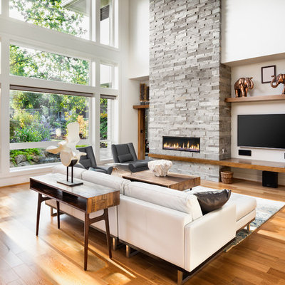 Inspiration for a contemporary medium tone wood floor and brown floor living room remodel in Los Angeles with white walls, a ribbon fireplace, a stone fireplace and a wall-mounted tv