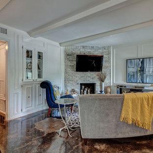Foto di un piccolo soggiorno classico aperto con pareti bianche, pavimento in cemento, camino classico, cornice del camino in mattoni, TV a parete e pavimento nero