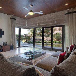 Bild på ett orientaliskt allrum med öppen planlösning, med vita väggar, en väggmonterad TV och vitt golv