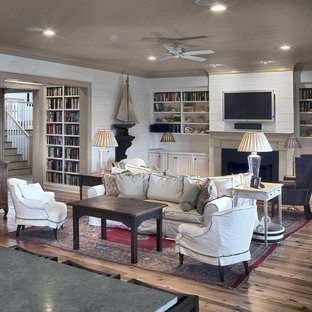 Coastal living room photo in Charleston with white walls, a standard fireplace and a wall-mounted tv
