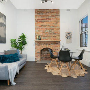 Transitional open concept living room in Melbourne with white walls, dark hardwood floors, a standard fireplace, a brick fireplace surround, no tv and brown floor.