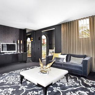 Modern inredning av ett mellanstort vardagsrum, med svarta väggar, en fristående TV och heltäckningsmatta
