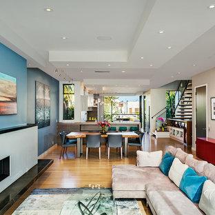 Exempel på ett modernt allrum med öppen planlösning, med ett finrum, blå väggar och en bred öppen spis