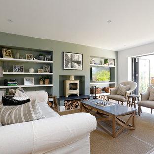Modelo de salón para visitas abierto, tradicional renovado, de tamaño medio, con suelo de madera clara, estufa de leña, marco de chimenea de yeso, suelo beige, paredes verdes y televisor colgado en la pared