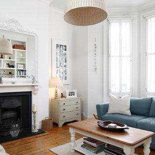 Idées déco pour un salon scandinave de taille moyenne et fermé avec un mur blanc, un sol en bois brun, une cheminée standard et un manteau de cheminée en bois.