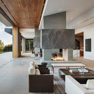 Immagine di un soggiorno minimalista aperto con sala formale, pareti bianche, pavimento in cemento, camino bifacciale, cornice del camino in cemento, nessuna TV e pavimento grigio