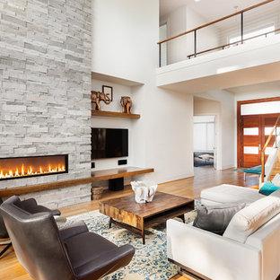 Idées déco pour un salon contemporain ouvert avec un mur blanc, un sol en bois clair, une cheminée ribbon, un manteau de cheminée en pierre, un téléviseur fixé au mur et un sol beige.