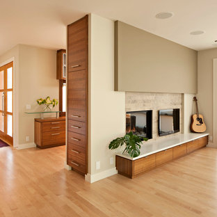 Minimalist light wood floor living room photo in Calgary with beige walls and a two-sided fireplace