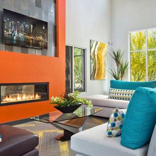 フェニックスの中くらいのコンテンポラリースタイルのおしゃれなLDK (オレンジの壁、カーペット敷き、両方向型暖炉、漆喰の暖炉まわり、壁掛け型テレビ、グレーの床、フォーマル) の写真