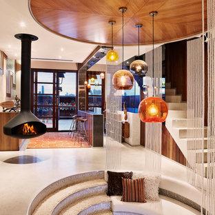 Imagen de salón abierto, contemporáneo, grande, con paredes marrones, suelo de cemento, chimeneas suspendidas, televisor colgado en la pared y suelo blanco