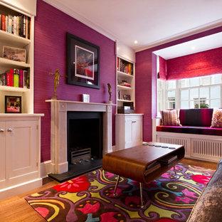 Esempio di un soggiorno minimalista di medie dimensioni e chiuso con pareti rosa, pavimento in legno massello medio, camino classico e cornice del camino in pietra