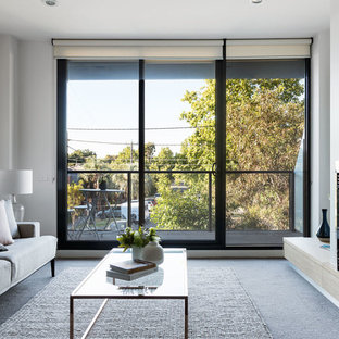 This is an example of a contemporary formal enclosed living room in Melbourne with white walls, carpet, a standard fireplace, no tv and grey floor.