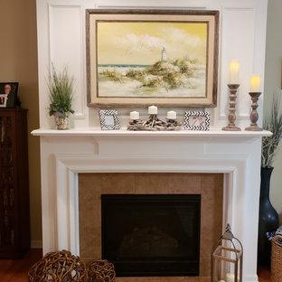 シカゴの大きいビーチスタイルのおしゃれなLDK (フォーマル、黄色い壁、ライムストーンの床、標準型暖炉、石材の暖炉まわり、据え置き型テレビ、茶色い床) の写真