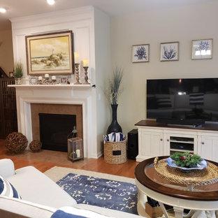 シカゴの広いビーチスタイルのおしゃれなLDK (フォーマル、黄色い壁、ライムストーンの床、標準型暖炉、石材の暖炉まわり、据え置き型テレビ、茶色い床) の写真